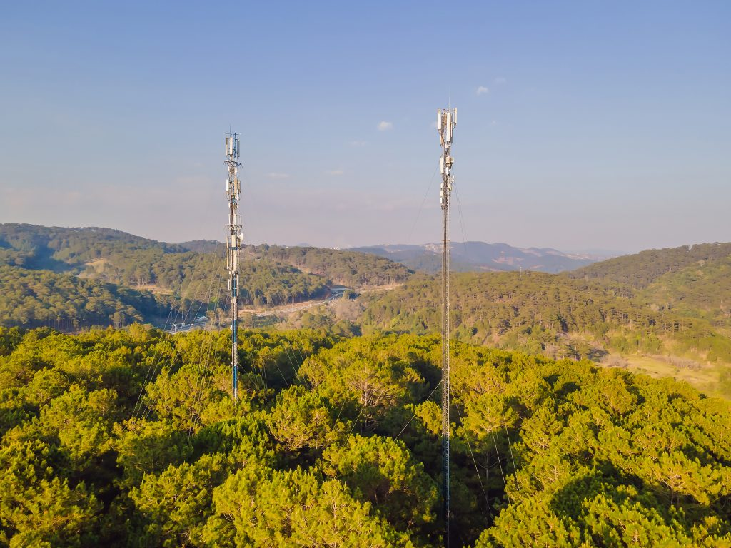 Aerial view of mobile phone antenna station tower in Swiss alps. Wireless communication in mountain area